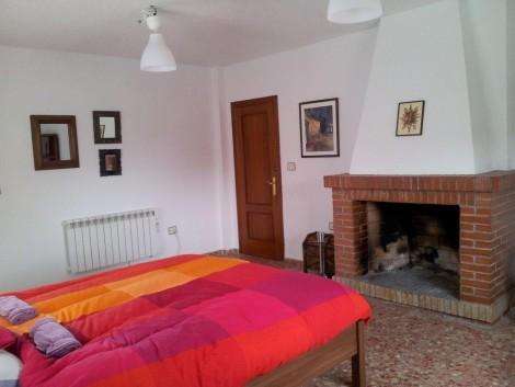 dormitorio rústico con calefacción de calor azul y chimenea en vivienda rural