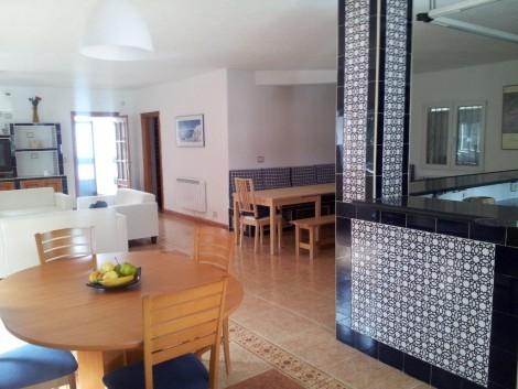 salon con chimenea cocina y dos mesas en alquiler vacaciones en Granada